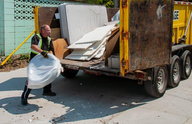 man throwing trash into a large dumpster rental. Dumpster bin reveals to be full of waste