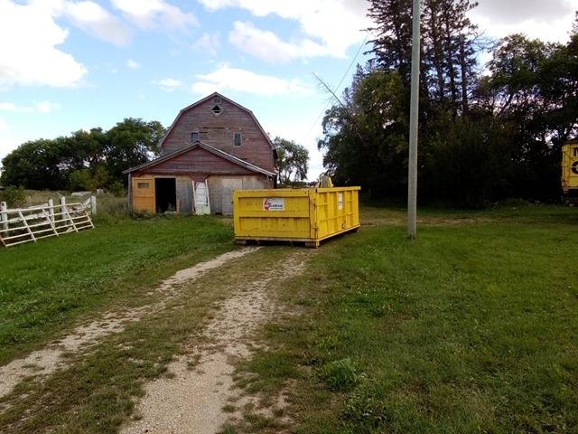 A yellow garbage bin located in a farm yard in front of an old barn